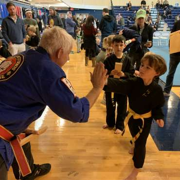 TJ breaking a board with Professor Chamberlain at the Kids Kenpo Martial Arts tournament at Episcopal School of Dallas