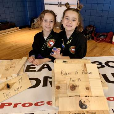 Elizabeth and Tilly at the board breaking table at the Kids Kenpo Martial Arts tournament at Episcopal School of Dallas