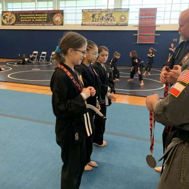 Shihan Shane and Adam congratulating winners at the Kids Kenpo Martial Arts tournament at Episcopal School of Dallas