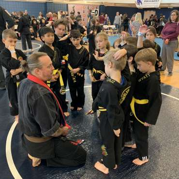 Adam Strickland addressing grapplers at the Kids Kenpo Martial Arts tournament at Episcopal School of Dallas